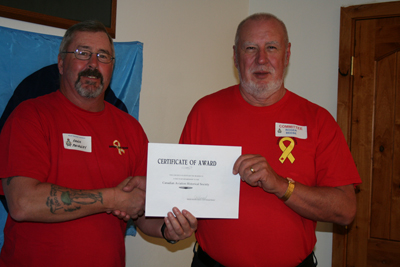 RCAF veteran Arnie MacCauley receiving a one-year CAHS membership from Roger Beebe