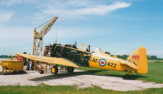 CHAA volunteers remove the engine from a Harvard Mk 4 during the 80th Anniversary celebration