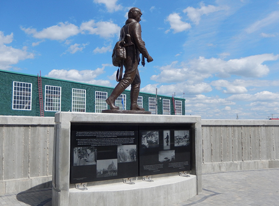 bronze statue depicts a wartime airman heading out to his aircraft as part of the RCAF Memorial