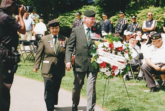 HooJung Jones Korean War veterans advocate and husband Don Kennedy present a wreath during the ceremony